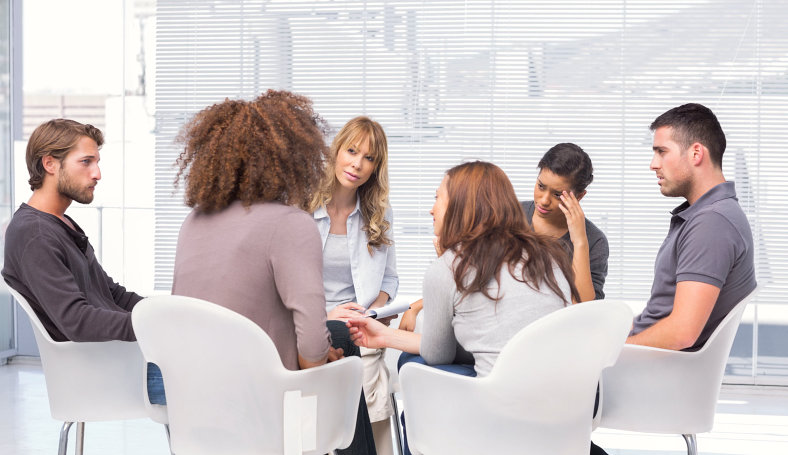 group of people having a discussion in a room